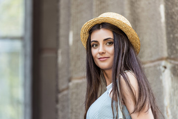 portrait of young beautiful woman in straw hat on street