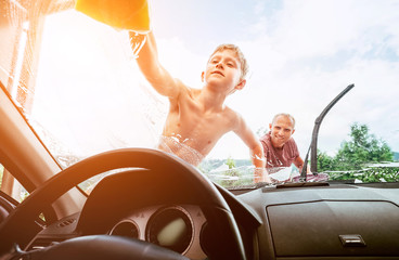 Son helps his father to wash a car