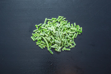 Heap of frozen green beans on a black background