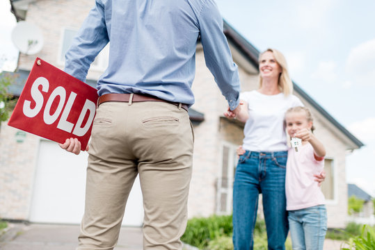 cropped shot of realtor with sold sign shaking hand of young woman with daughter in front of new house