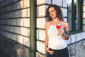 Portrait of a beautiful curly woman holding a glass of wine and leaning a wall of house in a vineyard during sunset