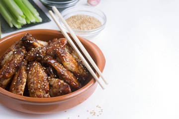 Traditional Asian stir fry chicken wings with sesame and vegetables. Copy space for text