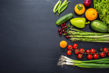Fresh vegetables and fruits organized against black background