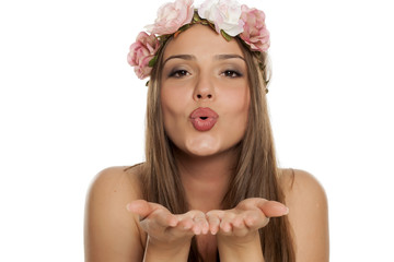 a happy young happy woman with a wreath of flowers on her head and kissing gesture on white background