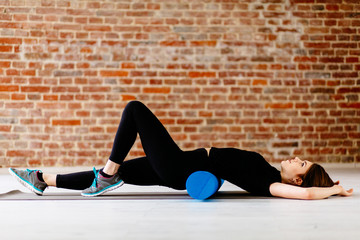 Fitness concept. Beautiful attractive fitness woman with foam roller under back  relaxing after workout on the exercising mat..Portrait of Active Tired Woman Using Blue Foam Roller loft interior.