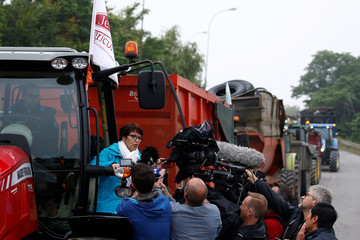 Christiane Lambert, President of France's farmer's union group FNSEA, talks to journalists as she stands on a tractor during a protest by French farmers to block the French oil giant Total refinery in Donges