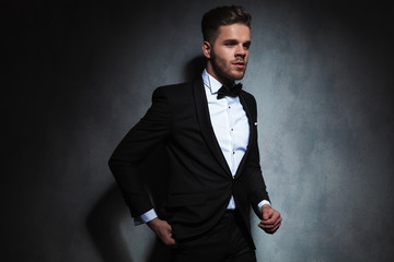 elegant man looks to side while standing near black wallpaper