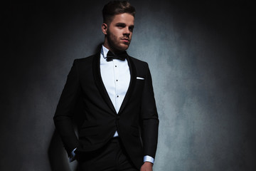 portrait of relaxed elegant man in tuxedo looking to side