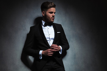 handsome unshaved man wearing black tuxedo looks to side