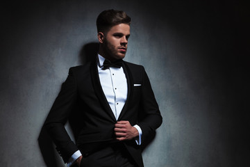 portrait of relaxed stylish man in tuxedo looking to side