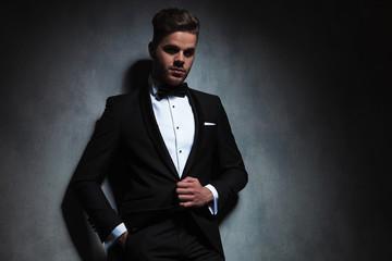 portrait of relaxed man unbuttoning his tuxedo black suit