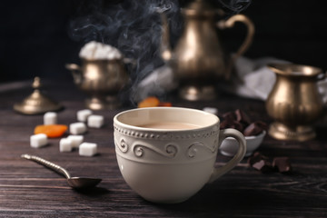 Cup of aromatic tea with milk on table