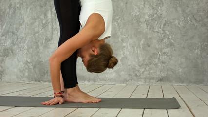 Side view portrait of beautiful model doing exercises sun solutation asana on gray mat