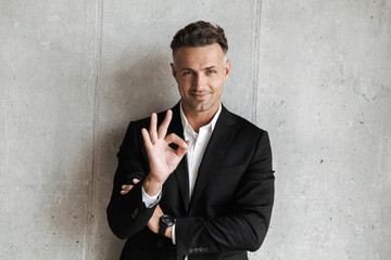 Handsome man dressed in suit showing ok gesture