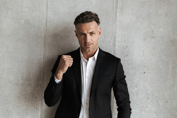 Handsome man dressed in suit showing his fist