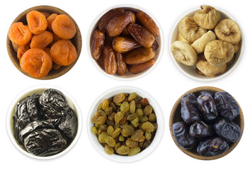 Collage of different dried fruits. Dried prunes, dried apricots, raisins, dates, figs isolated on white background. Top view. Dried fruits isolated on a white background.