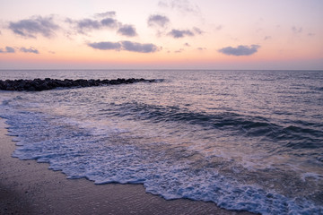 At the beach with rocks jutting out into the sea at the time before sunrise or after sunset