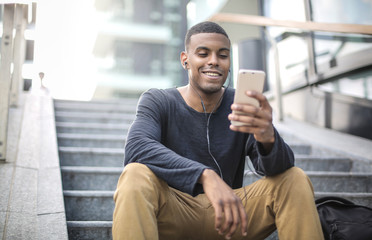 Guy sitting on the stairs, looking his phone and laughing