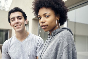 Friends listening to music together with earphones, portrait