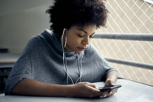Young woman looking at smartphone and listening to earphones