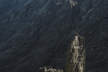 Aerial view of climber ascending a granite tower at last hours of the day