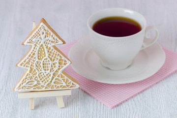 christmas tree gingerbread with coffe cup on wooden table with pink napkin