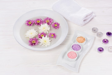 closeup view of bath for nails with flowers at table with towel, colorful sea salt and aroma candles for manicure and pedicure  in beauty salon