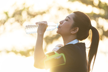 young sporty woman drinking water in the park.relaxing and exercise concept.
