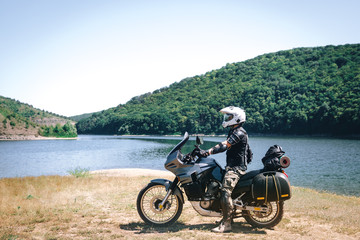 motorcycle driver adventure on the dirt beach of the mountain river, enduro, off road, beautiful view, travel equipment, bags and tent, dual sport, space for text