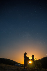 Silhouette of young couple under stars. The concept on the theme of love. romantic evening together, sunset, vertical photo, makes an offer to marry