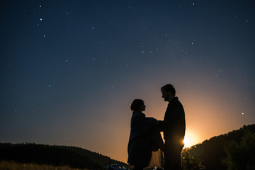 Silhouette of young couple under stars. The concept on the theme of love. romantic evening together, sunseto, makes an offer to marry