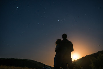 Silhouette of young couple under stars. The concept on the theme of love. romantic evening together, sunset
