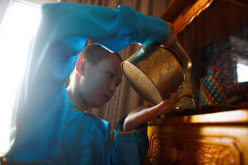 Young Buddhist monk Temuulen pours water into cups as a morning offering in his room before going to bed at the Amarbayasgalant Monastery in the Baruunburen district, Selenge province