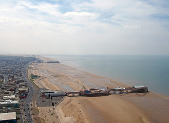 an aerial view of blackpool beach looking north showing the south and central piers at low tide with the main road and town stretching to the horizon on a bright summer day with blue sky and clouds