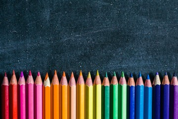 Pencils laid out in the color of the rainbow lie on a chalkboard