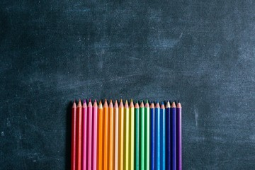 Sharpened pencils laid out by the color of the rainbow lie on the school Board