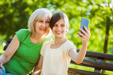 Grandmother and granddaughter are sitting in park and taking selfie.