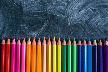 Sharpened Pencils in the Color of the Rainbow Spread out on a Chalkboard