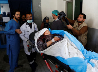 Men carry an injured woman at a hospital after a suicide attack in Kabul