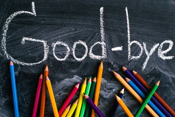 Colored pencils are scattered on the school chalk Board with the words good-bye