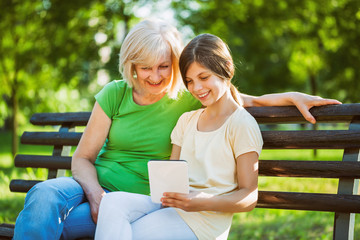 Grandmother and granddaughter are sitting in park and using digital tablet.