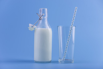 Glass bottle of fresh milk and a glass with a straw on a blue background. Concept of healthy dairy products with calcium