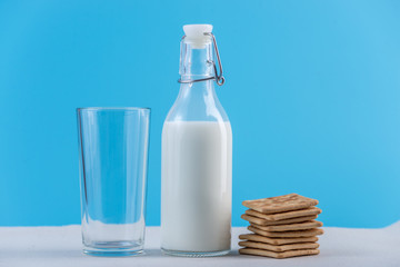 Glass bottle of fresh milk and cookies on blue background. Colorful minimalism. Concept of healthy dairy products