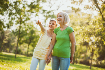 Grandmother and granddaughter are having fun together in park.