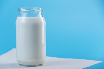 Glass bottle with fresh milk on blue background. Colorful minimalism. Healthy dairy products