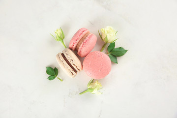 Tasty macarons and roses on light background