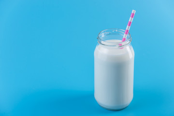Glass bottle of fresh milk with straw on blue background. Healthy dairy products with calcium