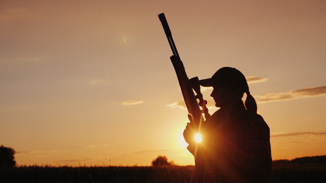 Beautiful silhouette of a woman with a rifle in the rays of the setting sun. Sports shooting and hunting concept