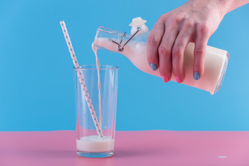 Woman's hand pours fresh milk from bottle into a glass on a pastel background. Concept of healthy dairy products