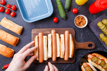 Image from above of man doing hotdogs on cutting board on table with sausages